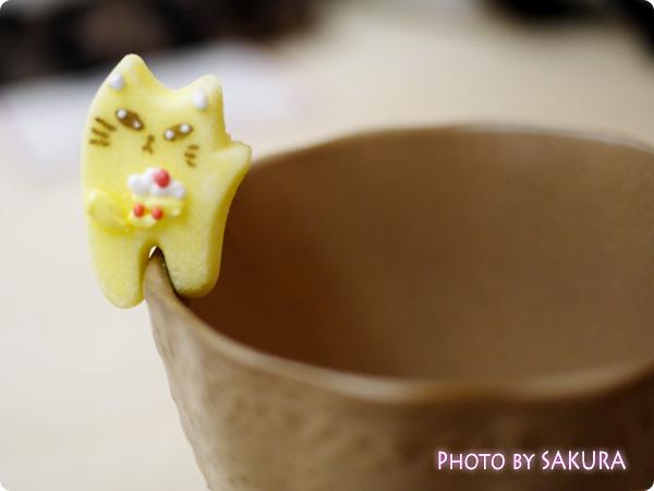 カップのふちでちょこんとごあいさつ ティータイムもあの子と一緒 にゃんにゃんシュガーの会 黄色の猫のお砂糖 手をあげてる猫 表