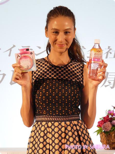 ファイテン「道端カレンの健康と美の秘訣」デザインしたRAKUWA磁気チタンネックレスと純金ピンクのおいしい水を持つ道端カレンさん